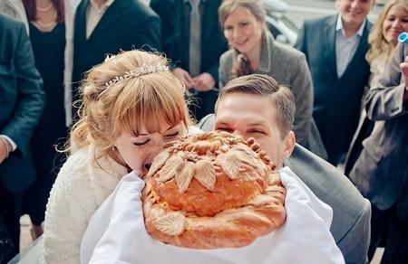 невеста и жених кусают каравай